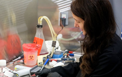 Laura Riva, Ph.D., a postdoctoral research fellow in the Chanda lab at Sanford Burnham Prebys, tests for compounds that may treat COVID-19.