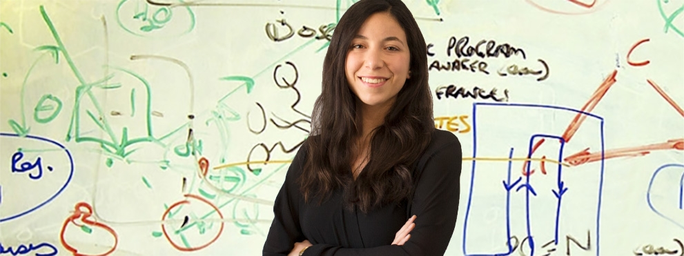Karina Barbosa, graduate student, in front of white board