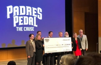 Garth Powis (fourth from left) who heads our National Cancer Institute (NCI)-designated Cancer Center—one of only seven in the nation—joined the beneficiaries onstage for a check presentation ceremony.
